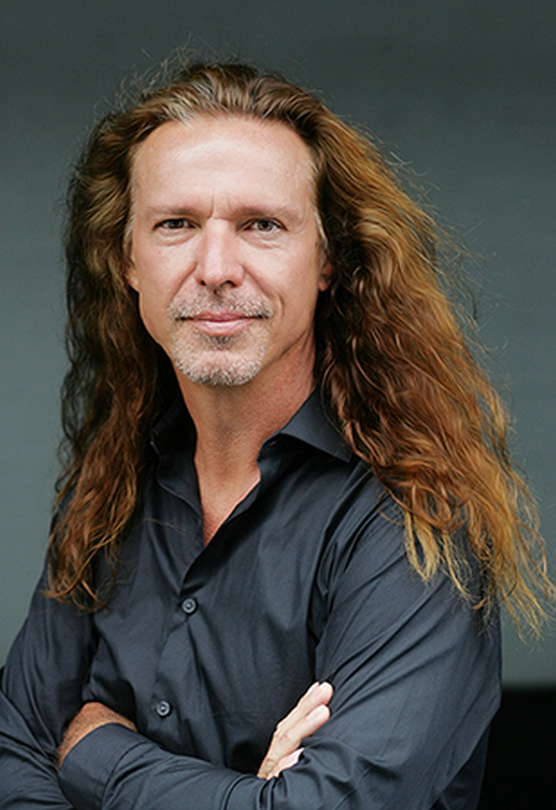 Un hombre rubio y pelo largo mira con una suave sonrisa