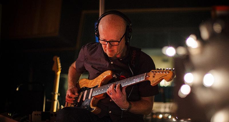 Un hombre calvo y con gafas que sentado interpreta su guitarra