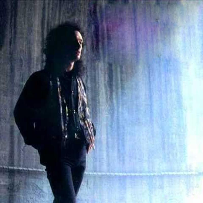 Un hombre joven con pelo largo que camina desprevenido
