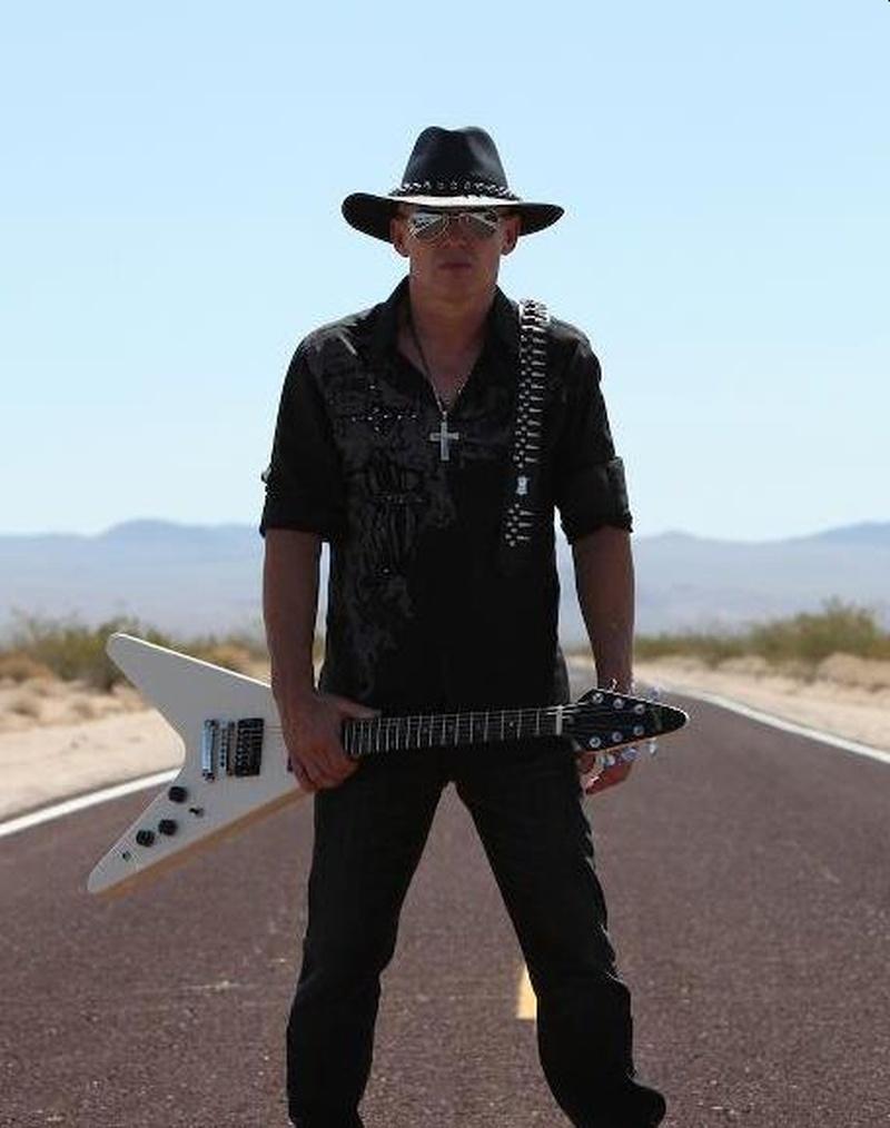 Un hombre vestido todo de negro con gafas y sombrero y una guitarra