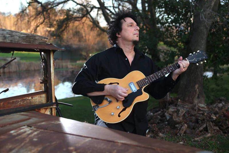 Un hombre con ropa oscura que toca su guitarra en un paraje agreste