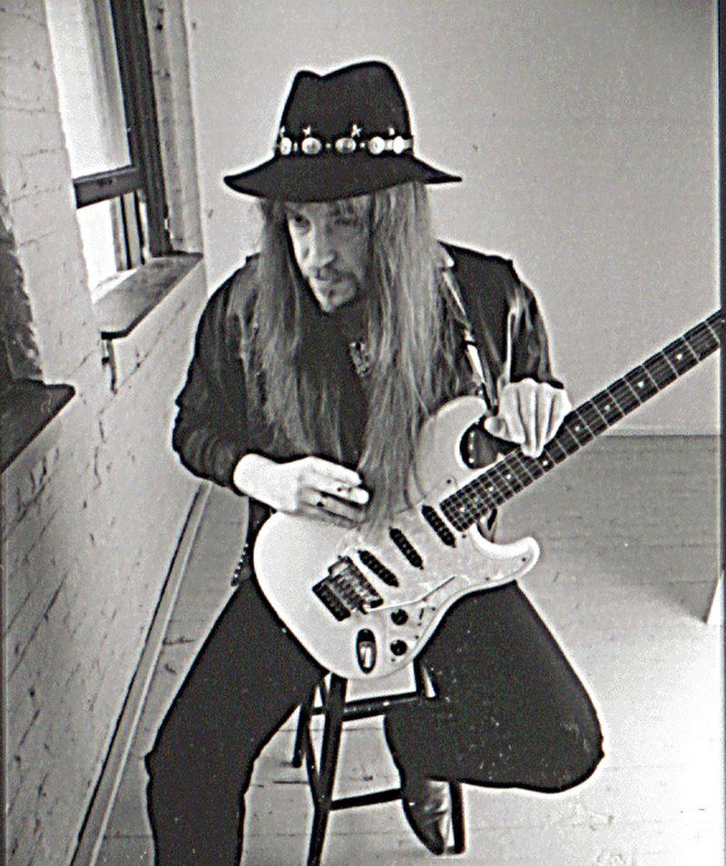 Una persona con ropa negra y sombrero negro que toca su guitarra