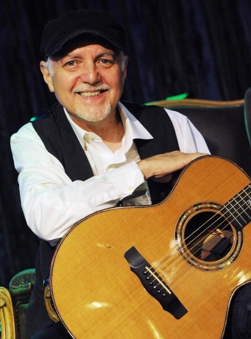 Un hombre algo mayor con una gorra y una linda sonrisa y su guitarra