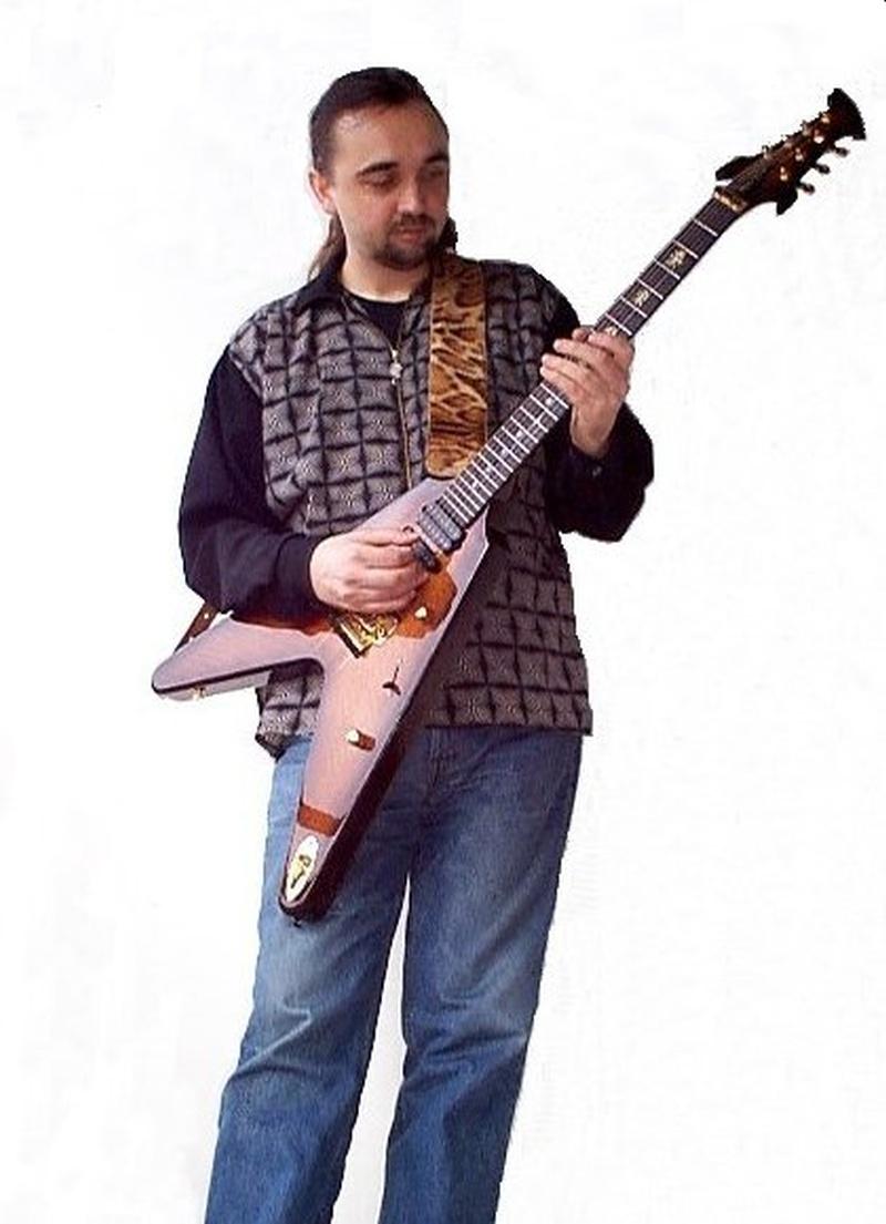 Un hombre con saco azul y sonriendo toca su guitarra