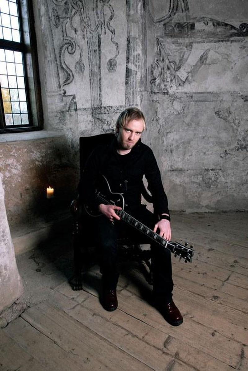 Un hombre en un lugar lúgubre con ropa negra sentado con una guitarra