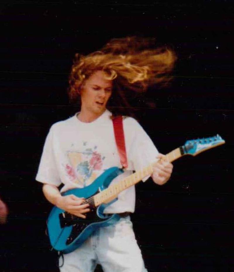 Un joven de pelo rubio y largo con ropa blanca interpreta su guitarra