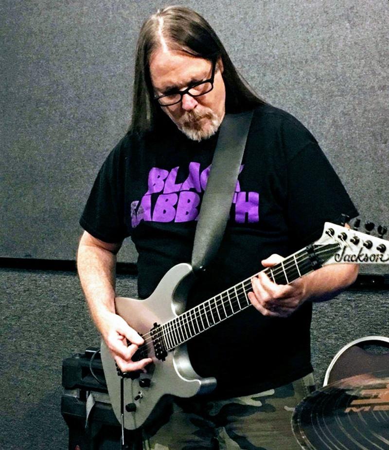 Un hombre mayor pelo largo y bigote  con lentes toca su guitarra