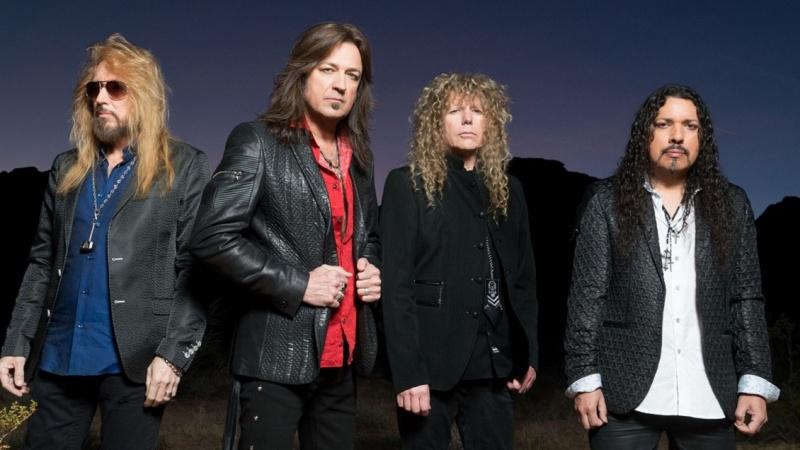 Cuatro hombres con chaquetas de cuero pelo largo mira hacia la camara