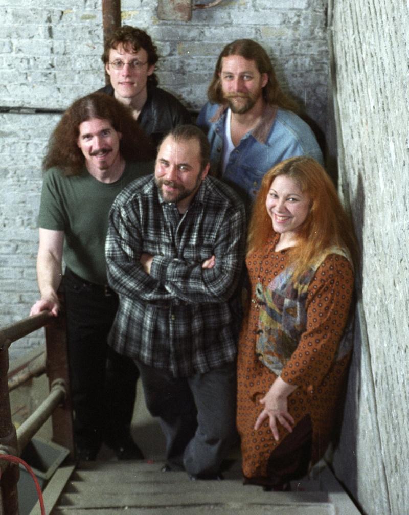 Cuatro hombres con pelo largo y una mujer  con ropa informal suben por una escala