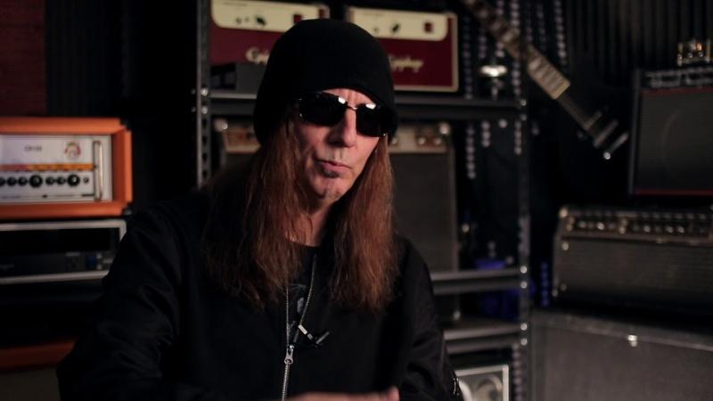 Un hombre con pelo largo gafas y gorro de motorista con su guitarra en un estudio de grabación