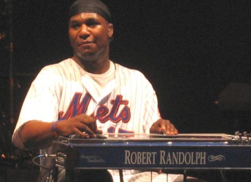 Un hombre afrodescendiente con una gorra toca un instrumento y sonríe
