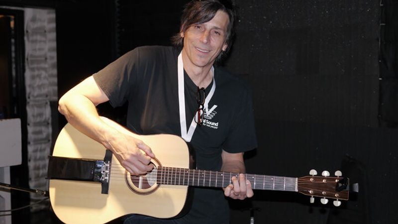 Un hombre con una guitarra y una expresión sonriente