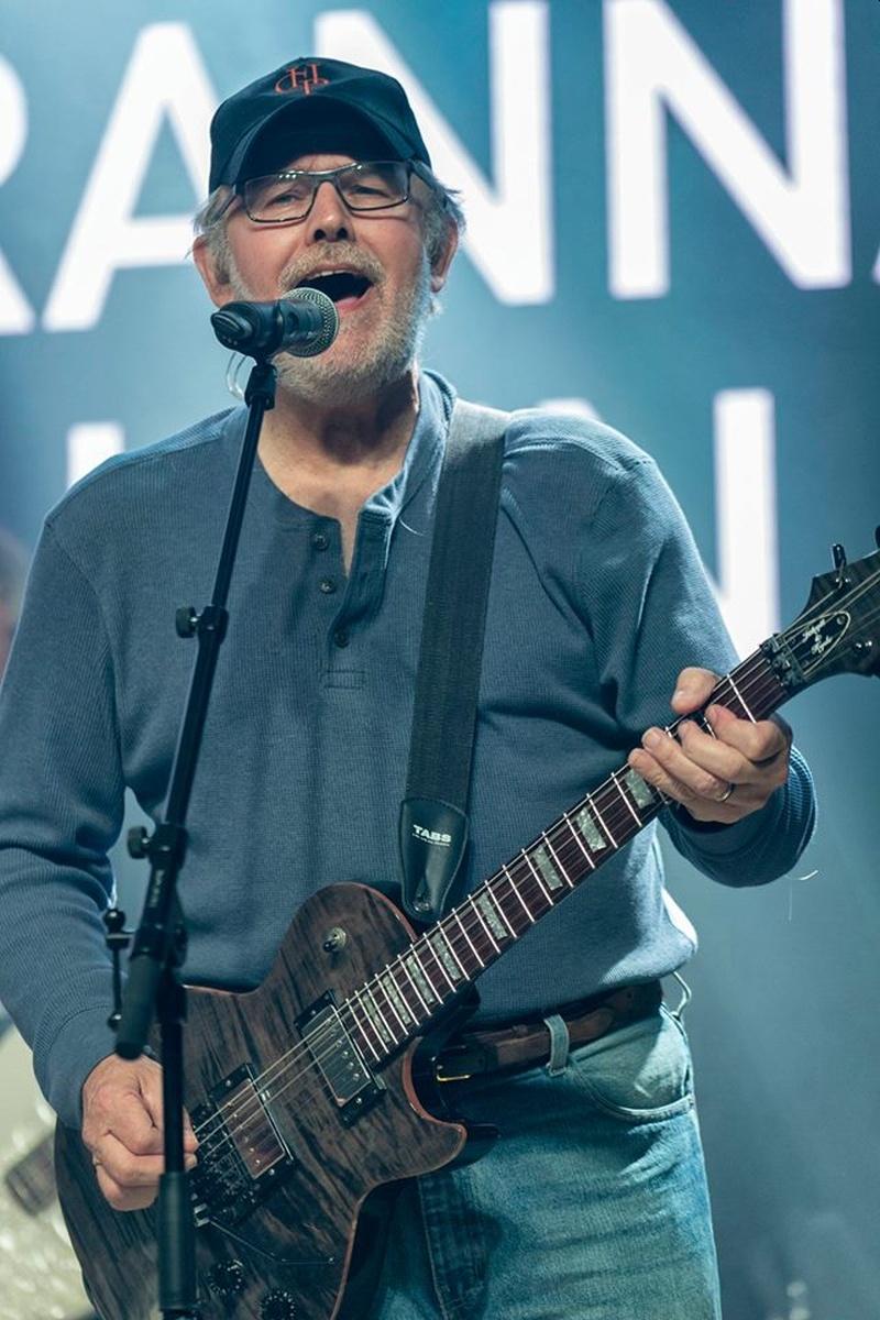 Un hombre mayor con gafas y gorra canta acompañado de su guitarra