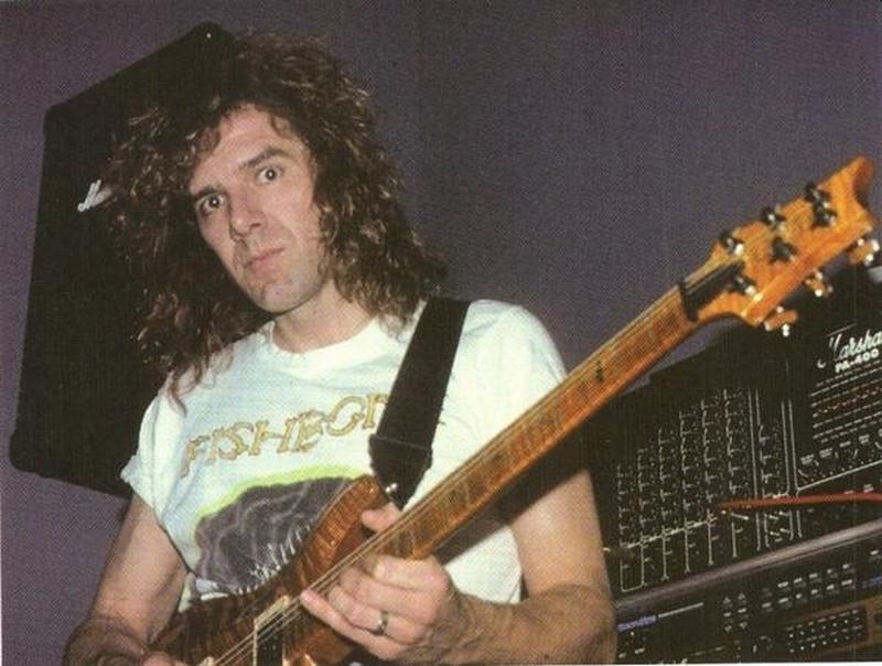 Con su guitarra tocándola y su pelo largo vemos a un músico  joven