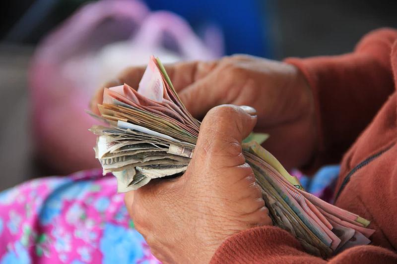 Tenemos una persona con unas manos trabajadas que  empuña un fajo de billetes