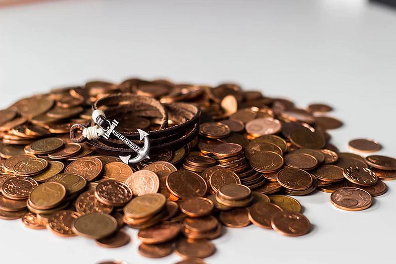 Vemos una cantidad de monedas de   color cobre  y sobre ellas una ancla y una correa