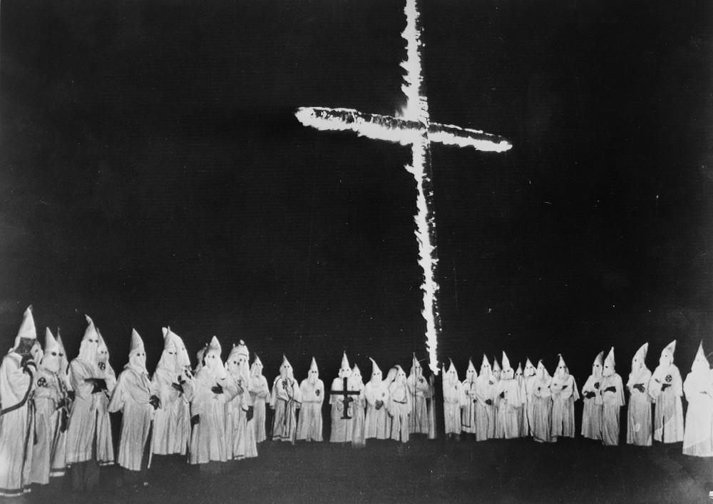 Un grupo de miembros del Ku Klux Klan observan una cruz encendida en llamas