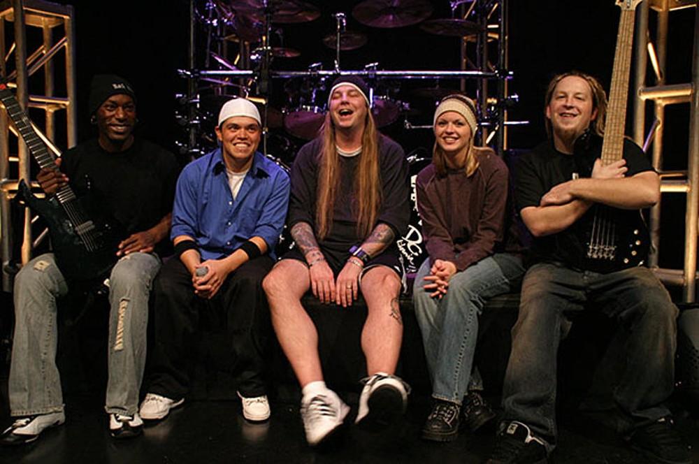 Una banda de rock sonriente sentada al lado de un escenario muy felices