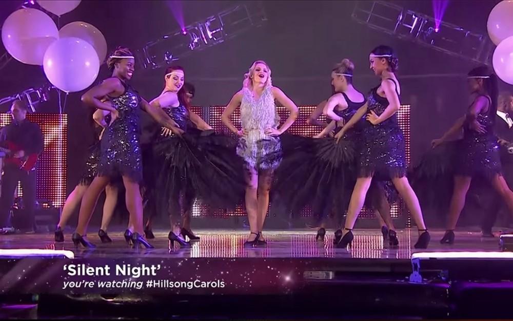 Un grupo de mujeres vestidas con ropa de los años 30s bailan en un escenario y se lee silencio en la noche