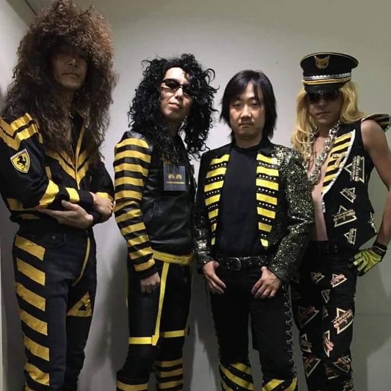 Cuatro integrantes de una banda con ropas negras con listas amarillas y triángulos y palabras