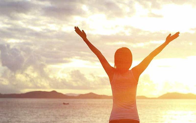 Vemos a una persona que levanta sus manos frente al mar admirando todo