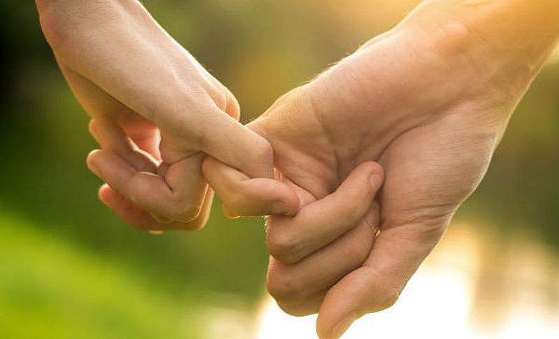 Vemos dos manos con dedos entrelazados