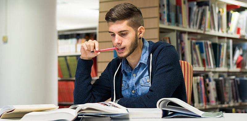 Vemos aun hombre joven en una biblioteca estudiando