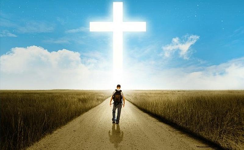 Vemos una carretera a ambos lados hay vegetación  un cielo azul y nubes  que forman una gran cruz