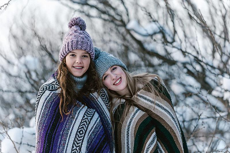 Vemos a dos mujeres  en un paisaje de invierno con ruanas y gorros de  frio