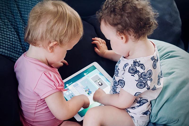 Dos bebes miran una revista muy entretenidos
