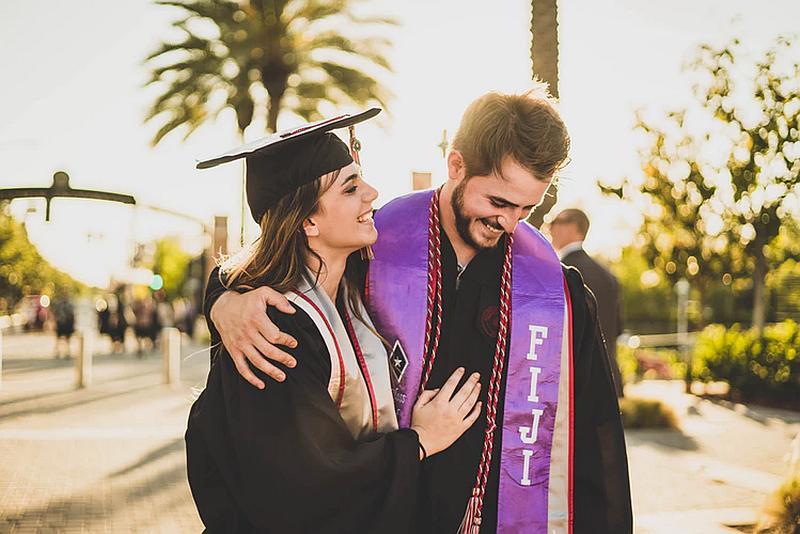 Vemos a una pareja de graduados  con sus togas y birretes  que caminan muy felices