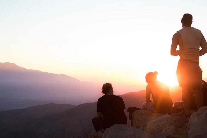 Varias personas contemplan una puesta de sol desde una montaña
