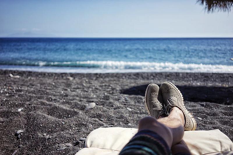Observamos los zapatos de alguien que observa el mar tranquilo desde la playa