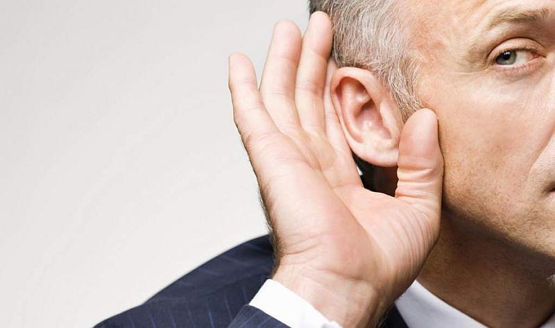 Un hombre canoso coloca su mano en su oído para escuchar mejor