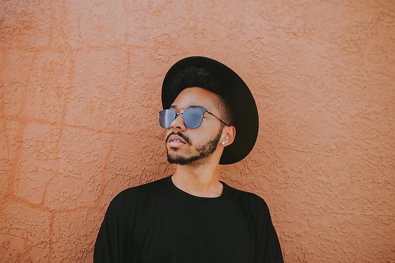 Vemos un hombre con un atuendo de sombrero negro con ala algo ancha y gafas que mira hacia arriba muy desprevenido
