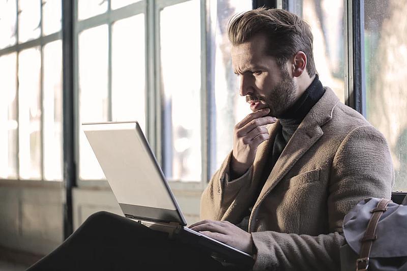 Vemos aun hombre con saco y cuello tortuga que mira su computador