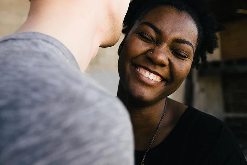 Vemos a un hombre que abraza a una mujer morena que sonríe feliz