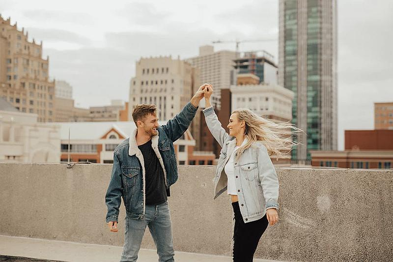 Vemos una   pareja que sonrie y disfruta al fondo se ven muchos edificios