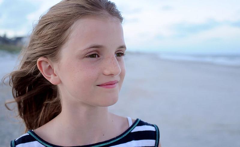 Vemos a una adolescente que mira el paisaje y sonrie