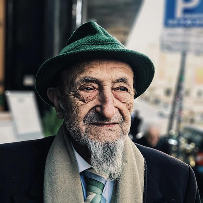 Vemos a un hombre muy mayor con una chivera larga y traje abrigo y bufanda de lana y sombrero que mira con nostalgia