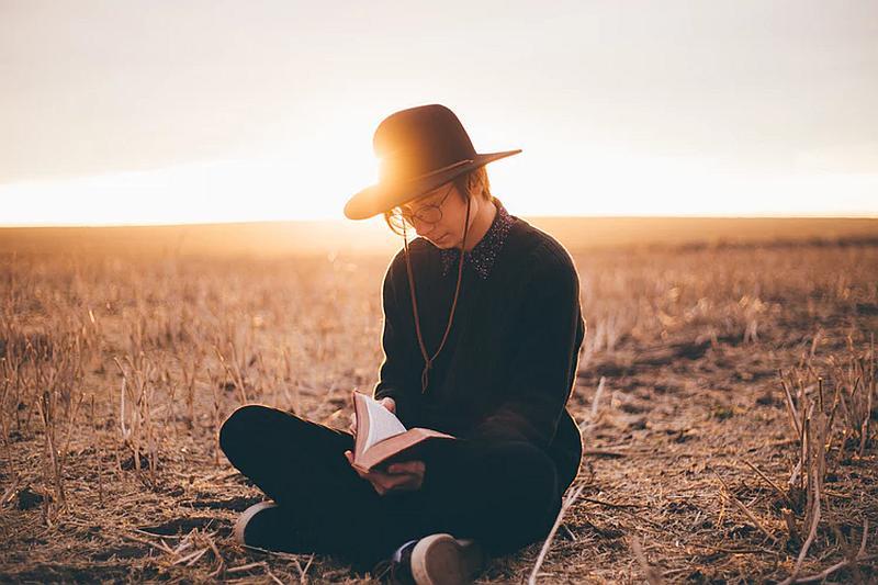 Vemos una persona sentada en la hierba que lee en el atardecer