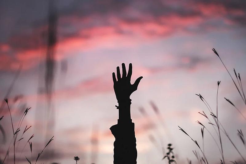 Vemos una mano en un paisaje de un atardecer