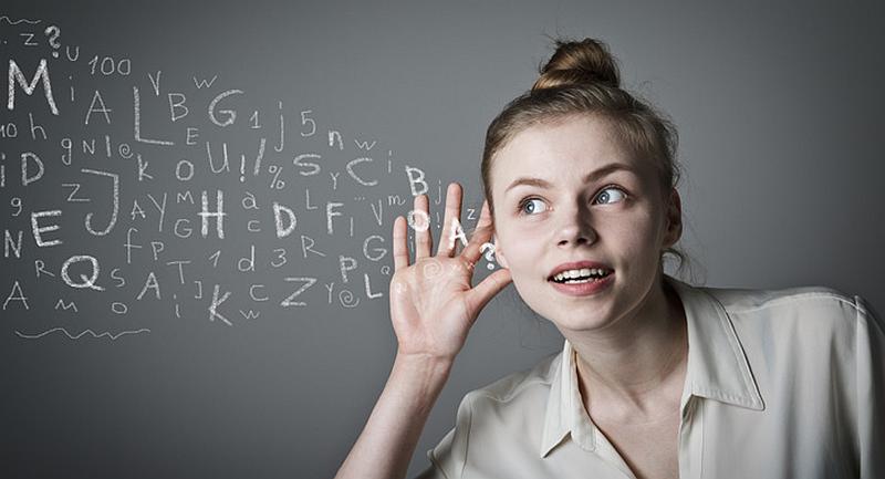 Vemos a una mujer rubia joven que colca su mano en el oído para  escuchar mejor frente a un tablero negro lleno de letras y numeros