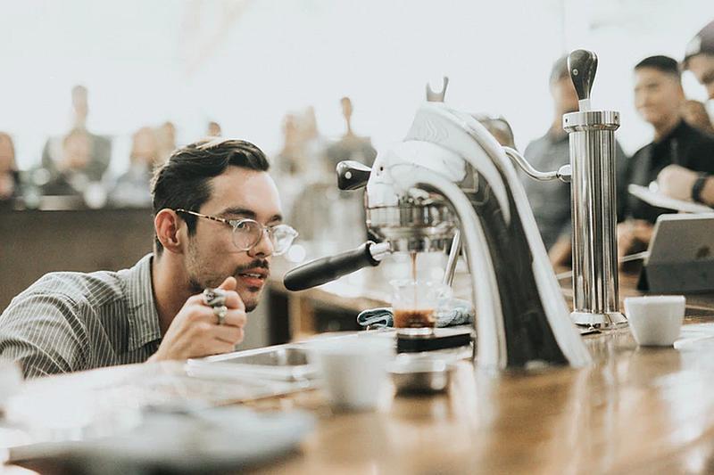Vemos un hombre joven con gafas que observa una maquina mientras cae e l café