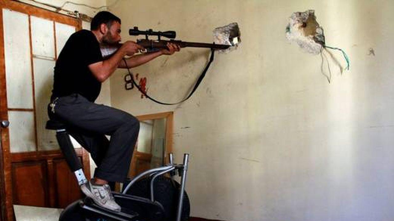 Hay un hombre joven subido en una escalera de donde con un rifle con mira y hay unos orificios en la pared de ahi mira el objetivo