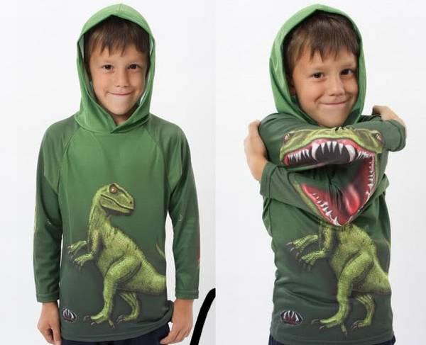 Un par de niños con buzos color verde con un  dinosaurio en un buzo está parado y en el otro buzo aparece en posición de ataque
