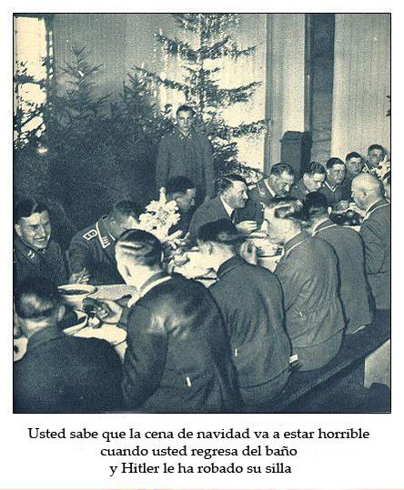 Una cena de navidad con gente con uniformes militares de una época pasada mientras un hombre de pie los observa