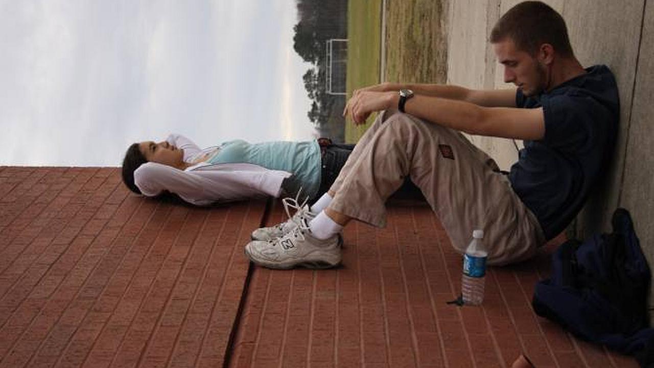Imagen de una mujer y un hombre  el tiene una botella de agua y está sentado