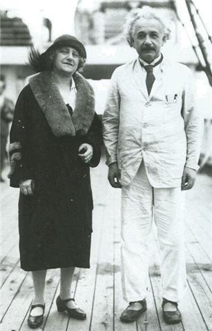 Una mujer con con abrigo y sombrero y un hombre con un traje claro sonrien