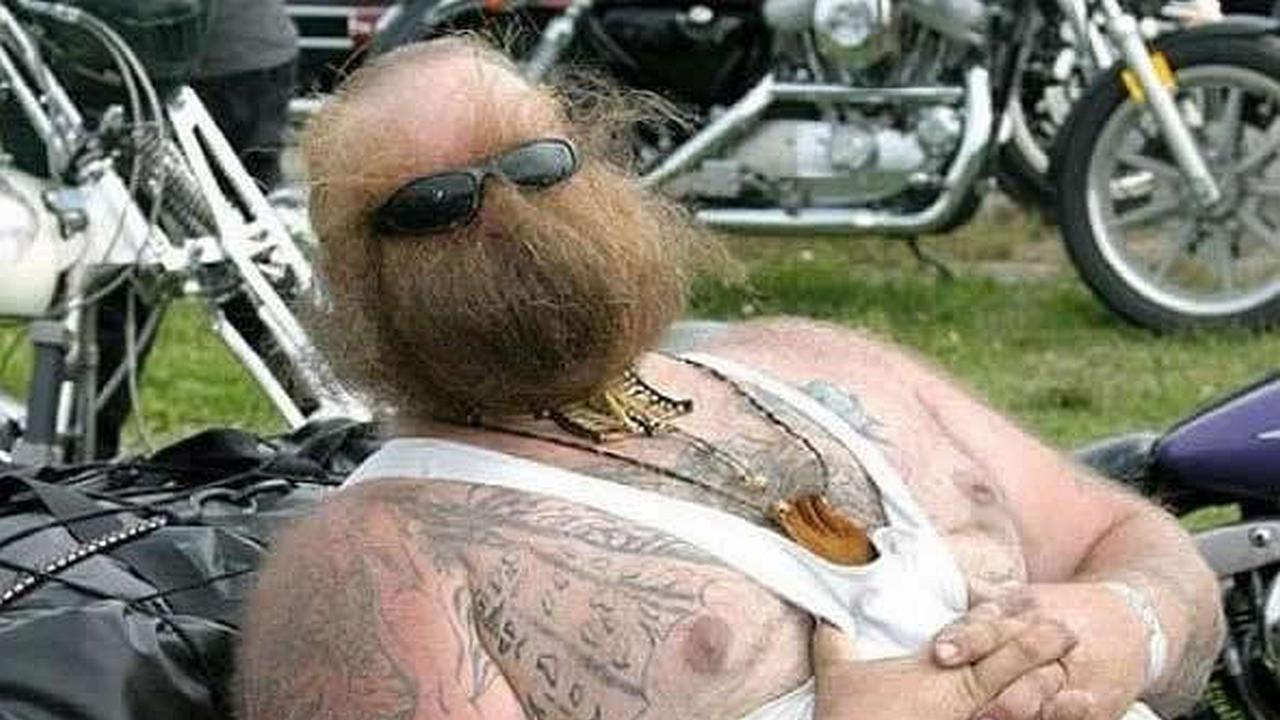 Un hombre con gafas y una barba que tapa toda su cara recostado en una moto